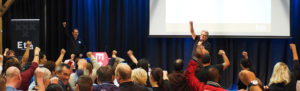 Two men onstage at a forum with fists raised, the audience raising fists.